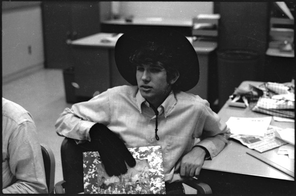 At the Boston University News Office: Peter Simon wearing hat and glove and holding copy of Rolling Stones', 'Their Satanic Majesties Request' , December 1967