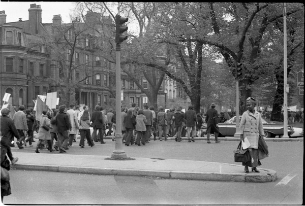 Vote With your Feet anti-Vietnam War protest march: woman watches while line of protestors march down the street: , November 9, 1968