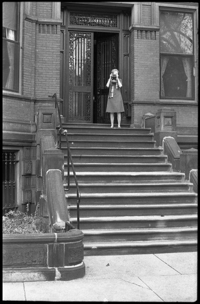 Vote With your Feet anti-Vietnam War protest march: woman in doorway photographing protestors: , November 9, 1968