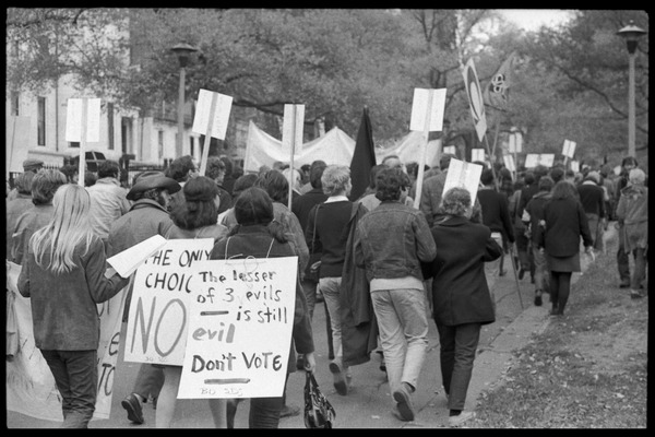 Vote With your Feet anti-Vietnam War protest march: Protesters marching in the streets above Boston Common with signs reading 'The lesser of 3 evils             is still evil -- Don't vote' and banners for SDS and New England Resistance: , November 5, 1968