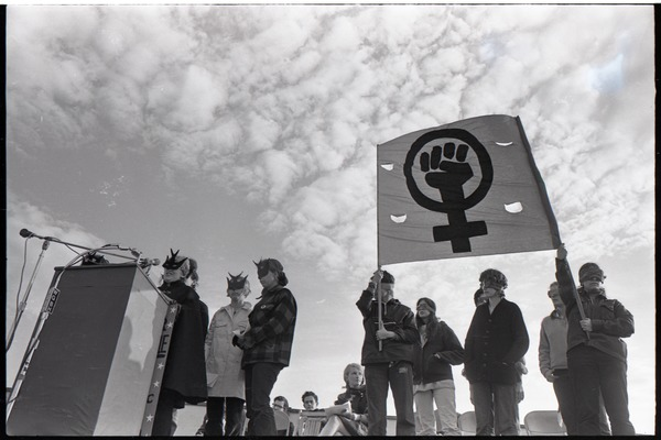 Anti-war rally at Soldier's Field, Harvard University: members of feminist group Bread and Roses wearing masks, speaking and holding a fist in a venus symbol, ca. May 8, 1970