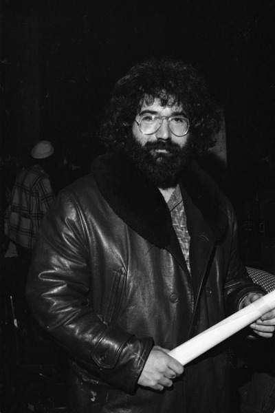 Grateful Dead performing at the Music Hall: Jerry Garcia backstage in a leather jacket and holding a rolled-up poster, April 1971