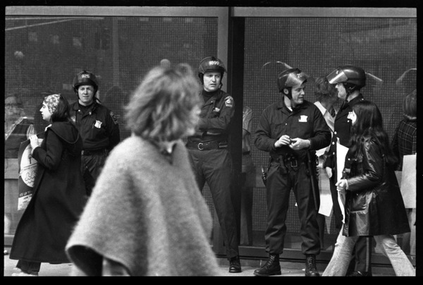 Police watch as antiwar demonstrators picket in front of the John F. Kennedy             Federal Building, ca. May 10, 1972