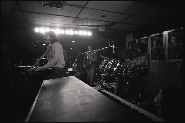 Jesse Colin Young at Paul's Mall: Young singing with Jeffrey Myer (drums), Marty David (bass), and Jim Rothermel (partially obscured) in background, October 1973