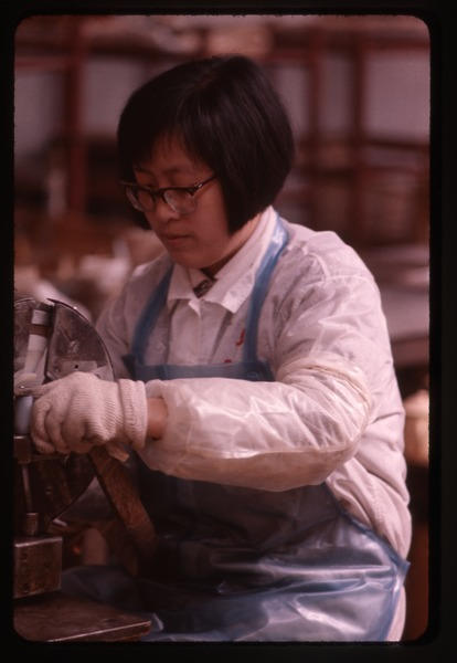 Woman working at machine, March 25, 1977