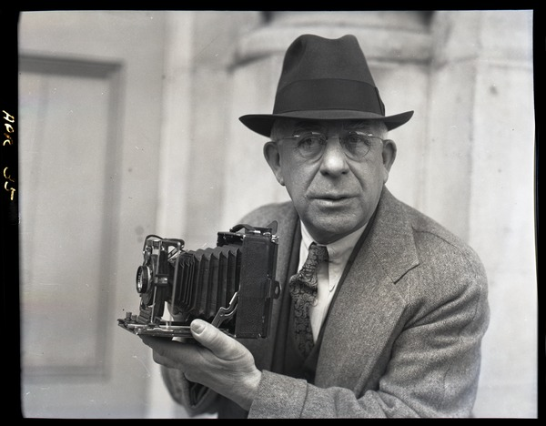 Sam Connor and Bob Emery: man posed with a Zeiss Ikon Super Ikonta camera, April 9, 1935