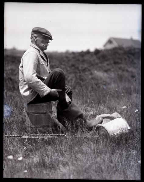 Otis Fish, the blind clam digger of Falmouth: portrait of Fish seated          on a overturned bucket, putting on his wading boots, ca. 1925