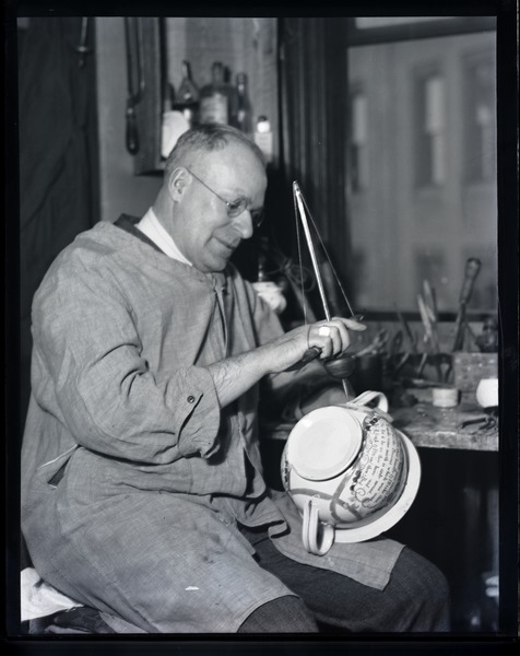Nathan S. Hill, china repairer, working on a transferware chamber pot, ca. 1925