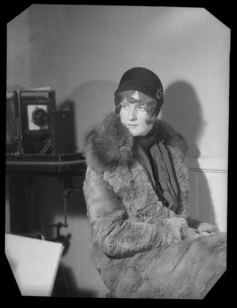 Mae Houston: portrait in a winter coat and cloche hat, large view camera in the          background, ca. 1928