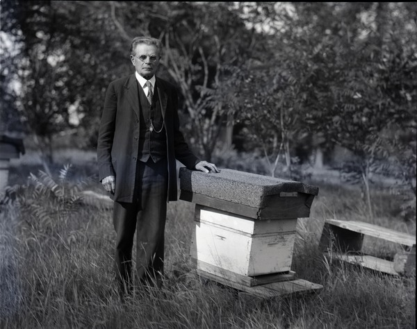 John Harvey Lovell: Full length portrait of noted bee expert, posed in the field with a hive: , ca. 1926