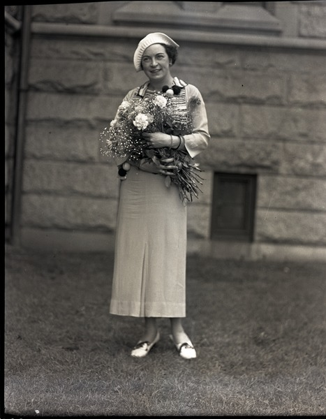 Kay Sennott: Full-length portrait holding bouquet at New Bedford Fire Chiefs' Convention: , ca. June 1935