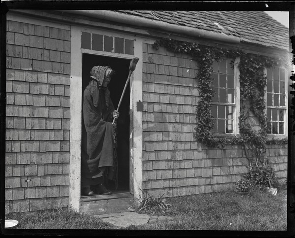 Reuben Austin Snow, the cross-dressing hermit of Cape Cod, wearing a shawl,          wielding a broom, and standing in the cottage doorway, ca. 1929