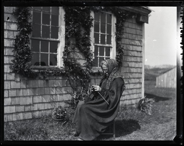 Reuben Austin Snow, the cross-dressing hermit of Cape Cod, seated in front of          cottage, knitting, ca. 1929