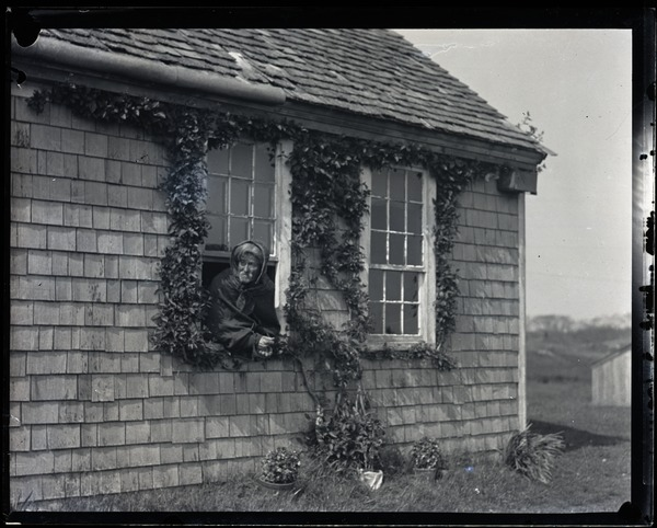Reuben Austin Snow, the cross-dressing hermit of Cape Cod, leaning out a cottage       window, ca. 1929