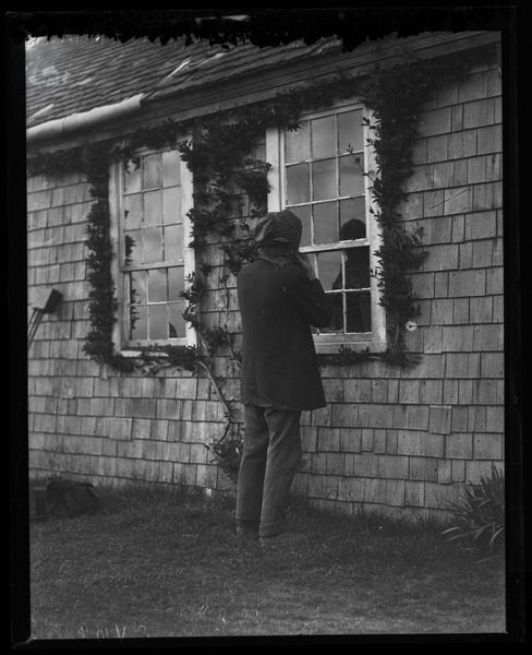 Reuben Austin Snow, the cross-dressing hermit of Cape Cod, looking in the cottage window, ca. 1929