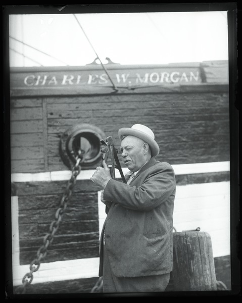 George Fred Tilton: Portrait of 'one of the last whaling captains' using a sextant with the Charles       W, Morgan: , ca. 1925
