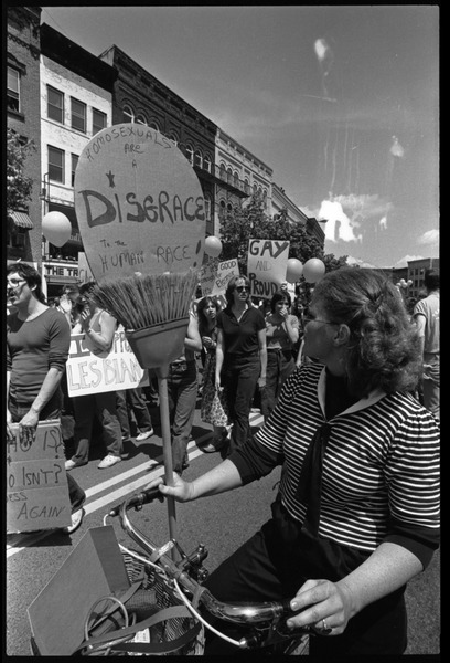 Crowd at the Northampton Pride Parade: crowd with signs on Main Street,             including opponent carrying sign 'Homosexuals are a disgrace to the human race', ca. 1983