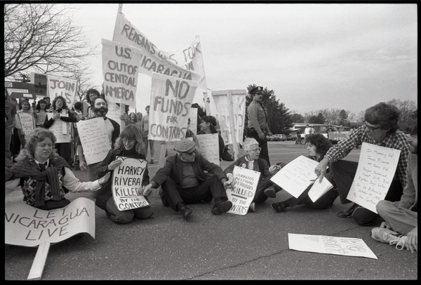 Protests against U.S. intervention in Nicaragua at Westover Air Force             base: protesters seated on the pavement, including Frances Crowe (third from right), ca. April 26, 1985