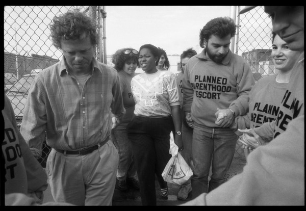 Escorts ushering a woman into the Planned Parenthood clinic in Providence, ca. October 1989