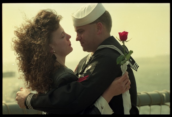 Woman with a rose embracing a sailor from the USS Roberts returning from Persian             Gulf War duty, ca. March 28, 1991