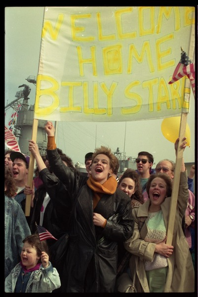 Ecstatic family with banner 'Welcome home Billy Stare,' as the USS Roberts returns from Persian Gulf War duty, ca. March 28, 1991