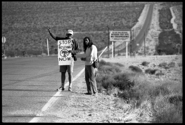 Activists standing by the road near entrance to the Nevada Test Site holding a sign reading 'Stop testing now,' at the Nevada Test Site peace encampment, May 1989