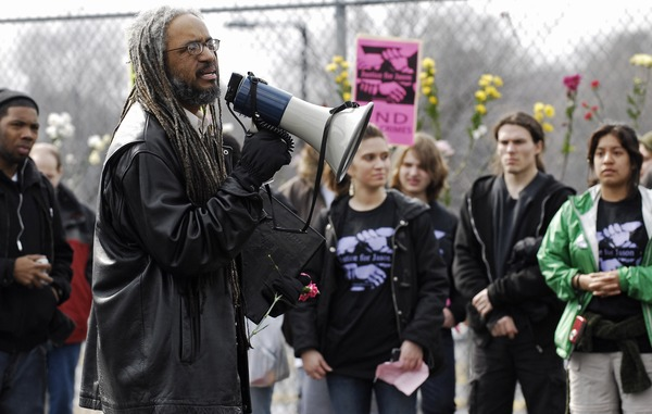Justice for Jason rally at UMass Amherst: Amilcar Shabazz, Chair of UMass             Afro-American Studies, speaks near a flower-filled fence, to students and staff who             rally in support of Jason Vassell, March 12, 2008