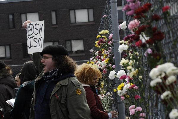 Justice for Jason rally at UMass Amherst: protesters in support of Jason             Vassell placing flowers in a chain link fence, March 12, 2008