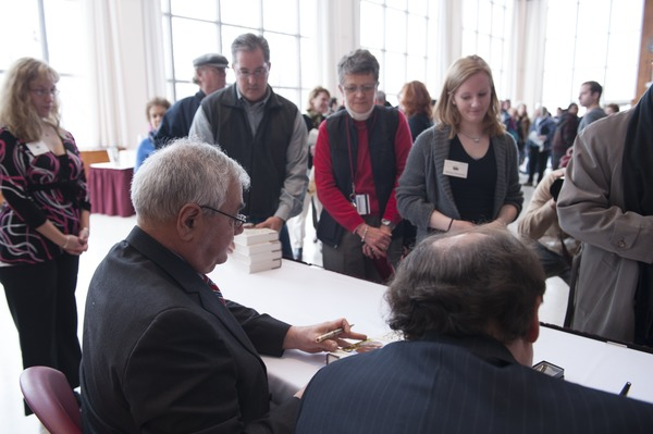 Congressman Barney Frank seated at a table in the Student Union Ballroom stage,             UMass Amherst, signing copies of his biography, ca. February 16, 2010