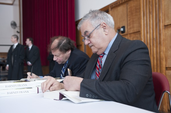 Author Stuart Weisman and Congressman Barney Frank (l. to r.) seated at a table in the Student Union Ballroom stage,             UMass Amherst, signing copies of his biography, ca. February 16, 2010