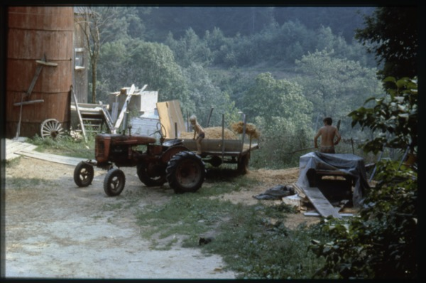 Spreading hay near the barn from a cart pulled by a tractor, Montague Farm Commune, ca. 1980
