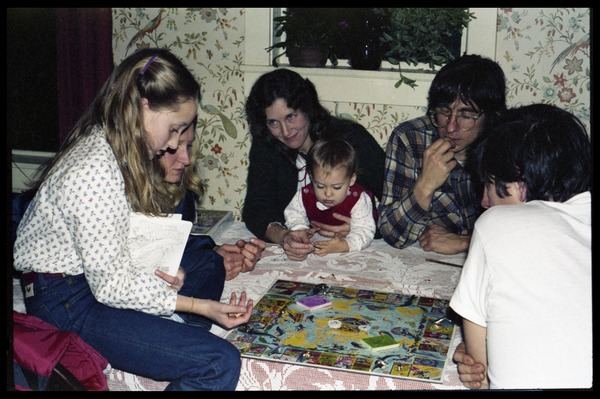 Playing a board game at Christmas time, Montague Farm commune: Group includes Sequoya Frey (far left), Harvey Wasserman (second from right): , ca. 1980