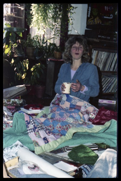Janice Frey, under quilts (probably on Christmas morning), Montague Farm commune, ca. 1980