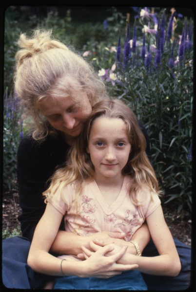 Janice Frey and daughter Sequoya, seated in front of blooming Liatris, Montague Farm Commune, ca. July 1980