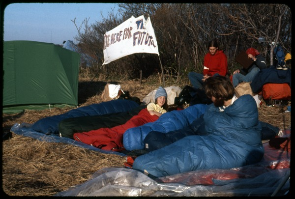 Waking up day 2: Occupation of the Seabrook Nuclear Power Plant: Occupiers waking up in sleeping bags and tents, with banner in background             reading 'We're here for the future': , ca. May 1, 1977