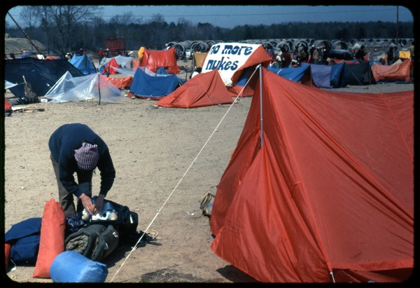 Packing up [before arrest]: Occupation of the Seabrook Nuclear Power Plant: Occupier stashing gear in backpack in front of tents (tent in the background             with large banner reading 'No more nukes'): , ca. May 1, 1977