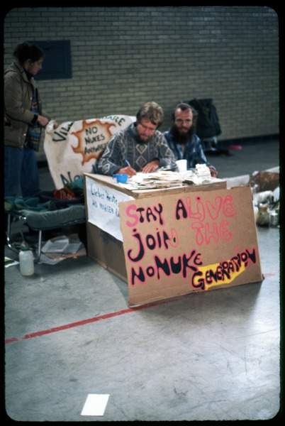Info booth: Occupation of the Seabrook Nuclear Power Plant: Booth set up on the armory floor with sign reading 'Stay alive join the no             nuke generation': , ca. May 1977
