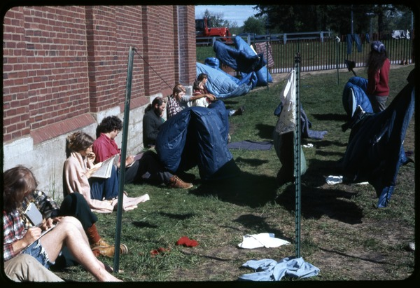 Enjoying sun while drying laundry: Occupation of the Seabrook Nuclear Power Plant: Occupiers sitting in the yard outside the armory, laundry hung nearby: , ca. May 1977