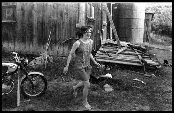 Cathy Rogers running barefoot past the barn, Montague Farm Commune, ca. 1974