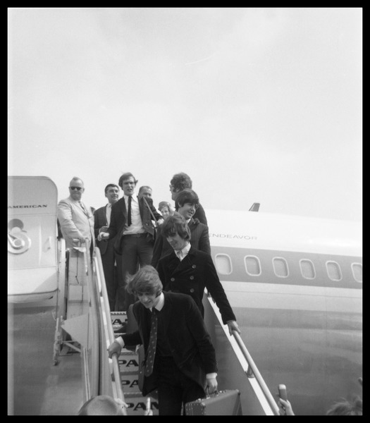 Ringo Starr, George Harrison, Paul McCartney, and John Lennon descending the ramp from a Pan             American airways Boeing 707, ca. August 1966