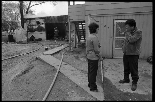 Man in anguish after learning that his garage was gutted by fire, and the family's cat was trapped inside: Firefighters tending to the smoldering shed as man looks on: , May 15, 1983
