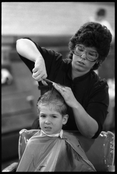 Young boy in a barber chair, enduring a haircut, 1983