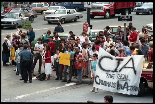 Anti-CIA protesters gathered at the corner of Main nd Gothic Street outside the Northampton Court House during the CIA             protest trial: Protesters carry a banner reading 'CIA, the real criminals in action' and             other signs: , April 16, 1987