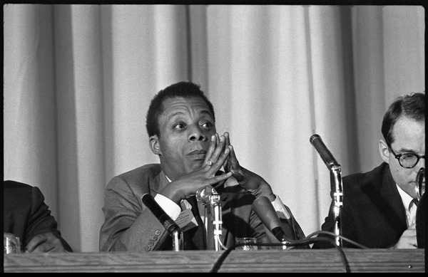 James Baldwin speaking as part of a panel at the Youth, Non-Violence, and Social Change             conference, Howard University: View of Baldwin seated at a table, William Sloan Coffin (partly obscured) at             right: , November 5, 1963