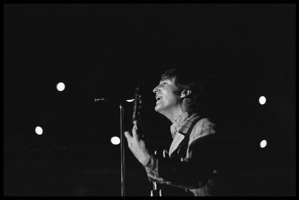 John Lennon (the Beatles) playing guitar and singing in concert at D.C. Stadium, August 15, 1966