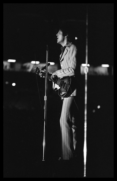 Paul McCartney (the Beatles) playing bass and singing in concert at D.C.             Stadium: full-length portrait, August 15, 1966