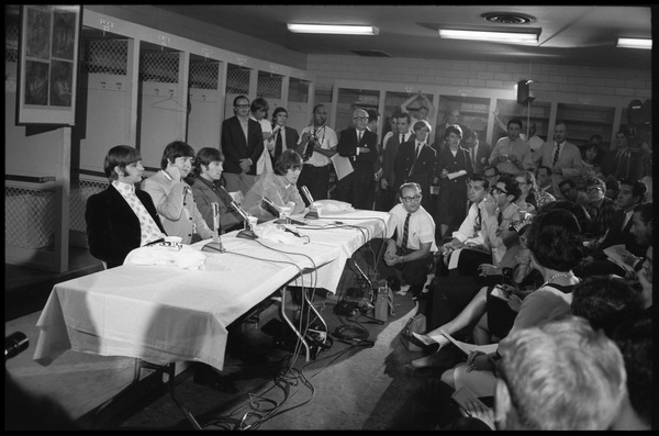 Ringo Starr, Paul McCartney, John Lennon, and George Harrison (l. to r.) seated at a table during a Beatles press conference, August 15, 1966