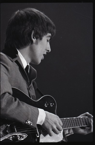 George Harrison playing guitar in concert with the Beatles, Washington Coliseum, February 11, 1964
