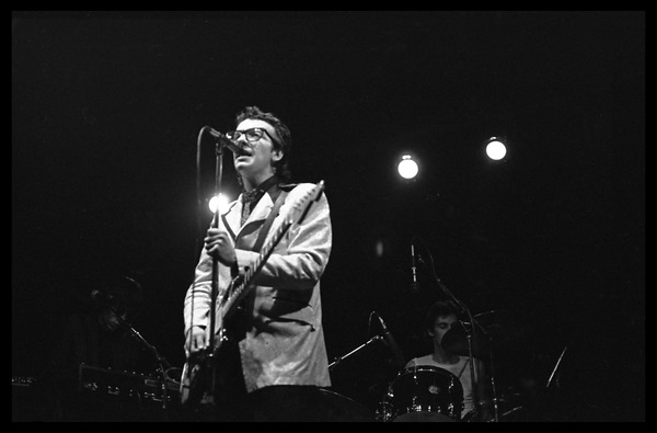 Elvis Costello and the Attractions in concert: Elvis Costello at the microphone,             with Steve Nieve (keyboards) and Bruce Thomas (drums), March 1, 1979