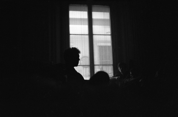 Bob Dylan silhouetted against a window, playing a guitar backstage, Newport Folk Festival, July 1963
